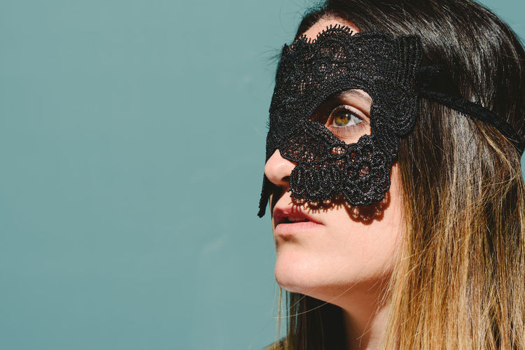 Woman wearing eye mask against blue background