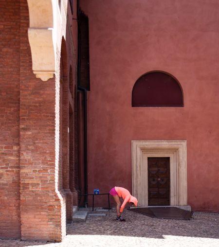 Woman walking by red door