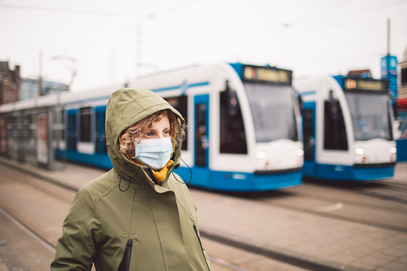 Woman wearing mask standing against trains