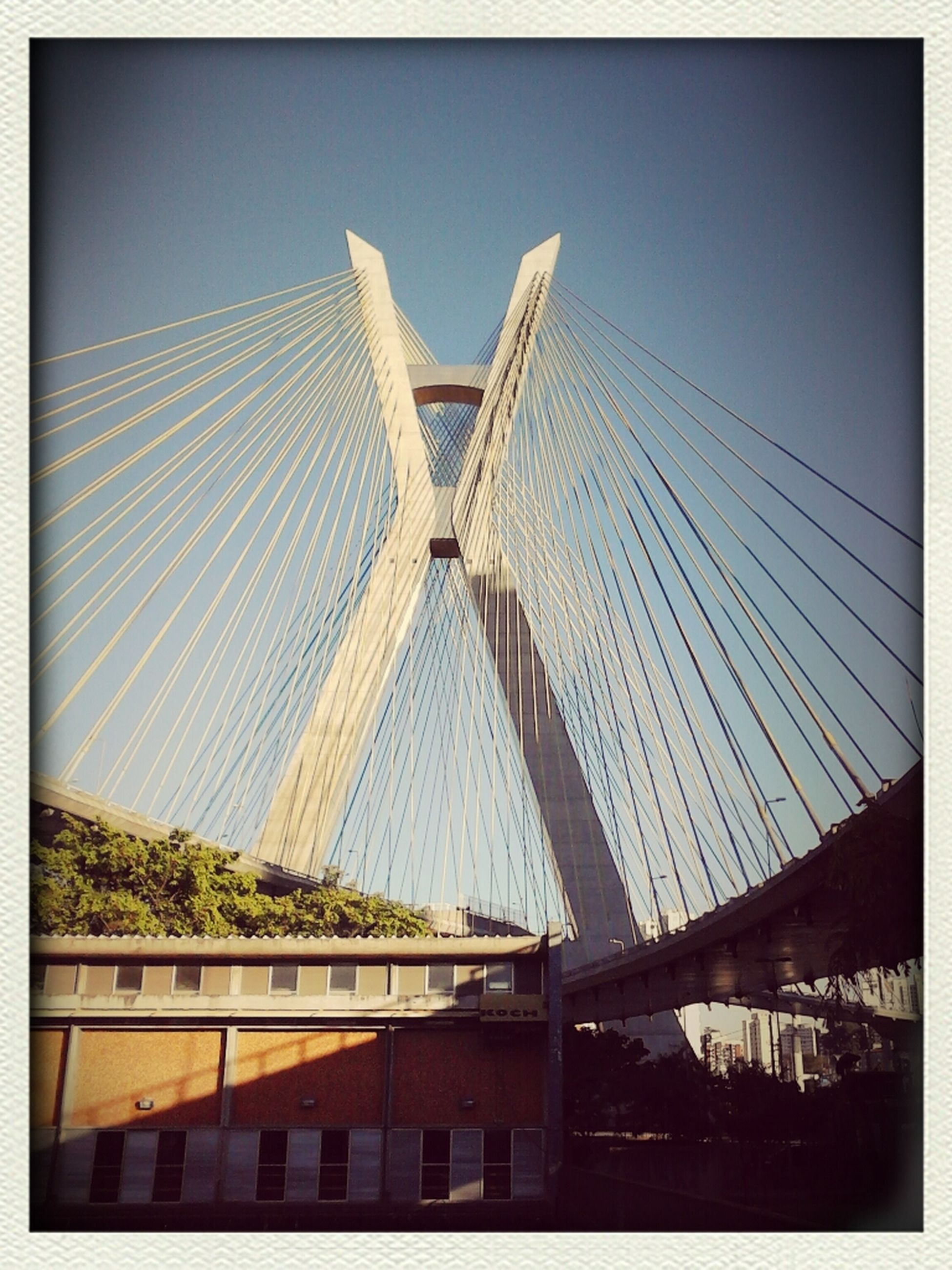 architecture, built structure, transfer print, building exterior, low angle view, auto post production filter, clear sky, bridge - man made structure, city, connection, sky, modern, engineering, day, outdoors, no people, bridge, roof, building, office building