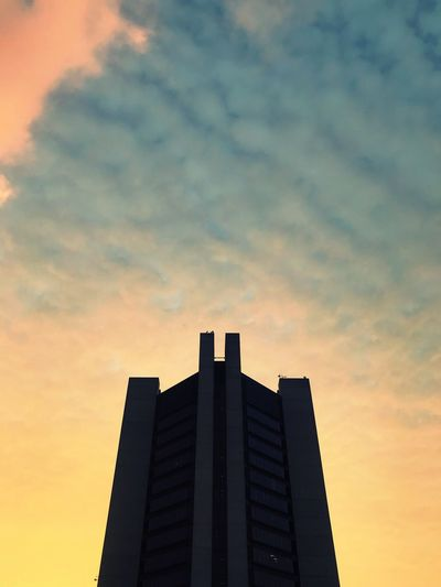 Low angle view of skyscraper against sky during sunset