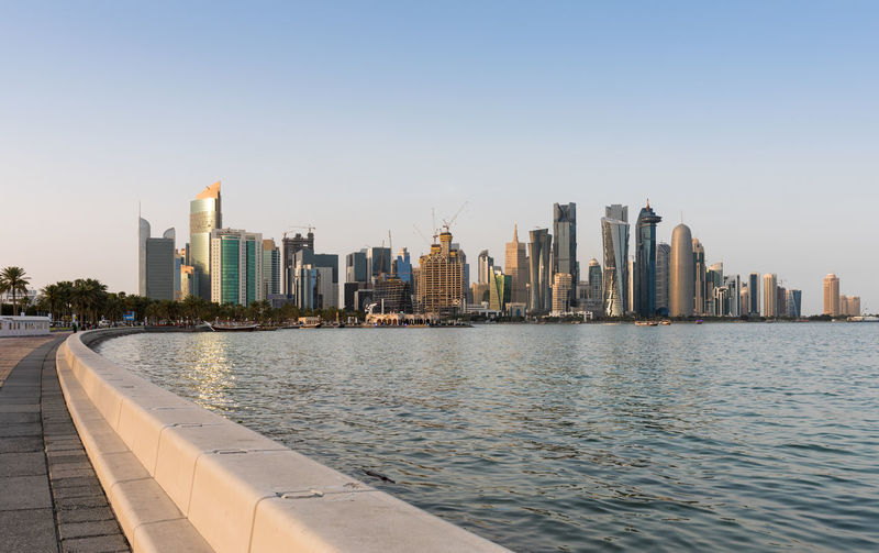 The skyline of Doha seen from the Corniche Street, Qatar Architecture Building Exterior Built Structure City City Life Cityscape Clear Sky Corniche Doha Downtown District Financial District  Modern No People Outdoors Qatar Sky Skyscraper Travel Destinations Urban Skyline Walkway Water Waterfront