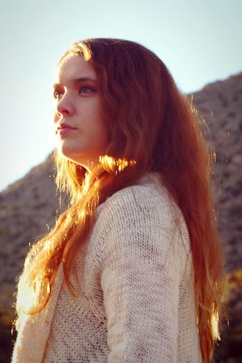 Young Woman With Long Brown Hair Standing Against Mountain