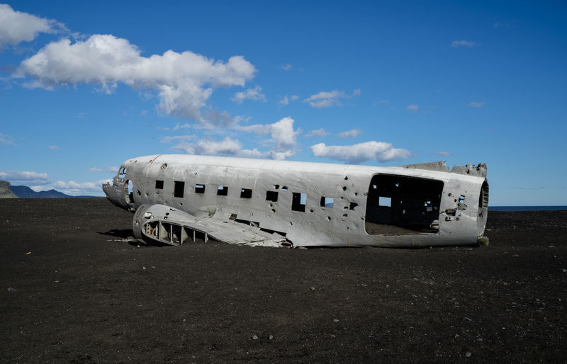 Damaged Airplane On Mountain Against Blue Sky