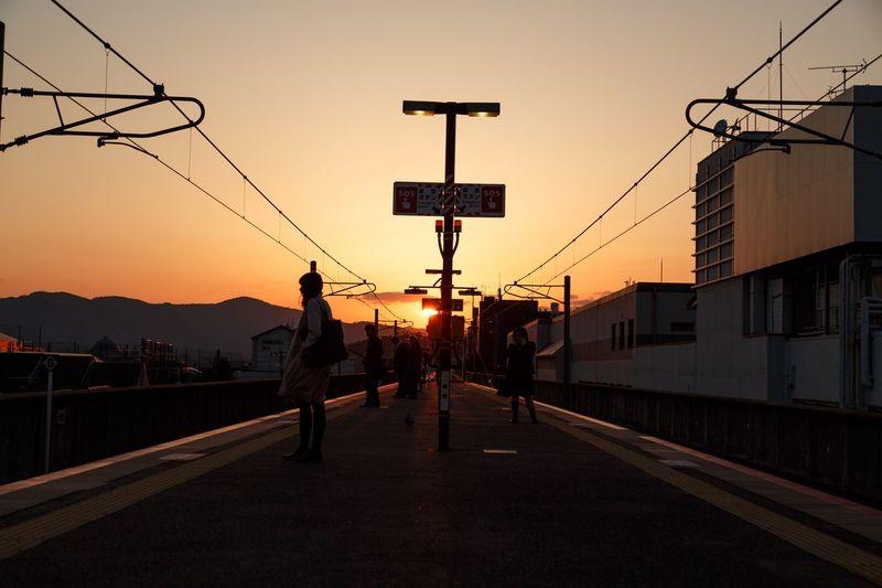 Silhouette men on bridge against sky at sunset