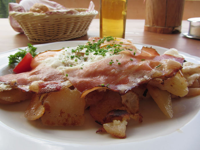 Typical South Tyrolean dish with speck, fried eggs, potatoes and chive Speck Fried Tyrol Potato Egg Chive Italian Food Alto Adige Tyrolean Smoked Bacon Ham Cold Cuts Snack Cut Appetizing  Dine Speciality Rustic Eat Tasty SLICE Hot Gourmet Dinner