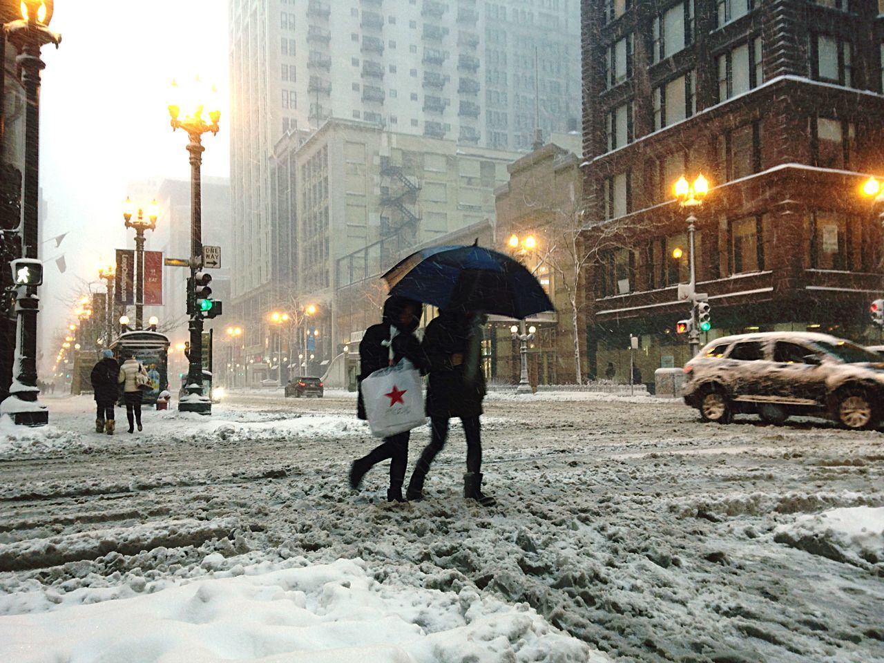 People crossing snow covered city street