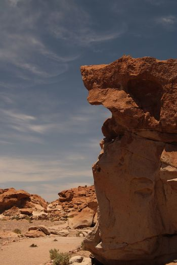Rock formation against cloudy sky