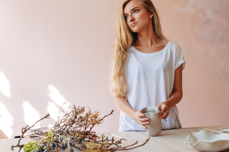Beautiful young woman looking away while carving on pot over table