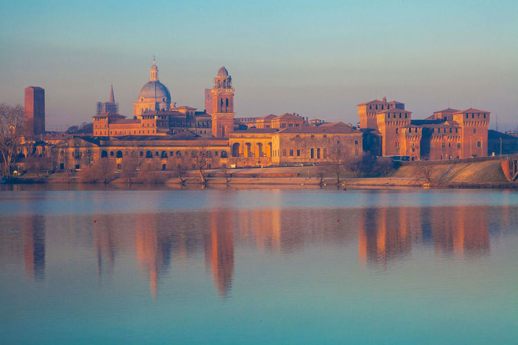The skyline of city of mantova italy at sunrise reflected on waters of river mincio