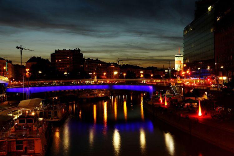 Illuminated Bridge Over Danube River In City At Night
