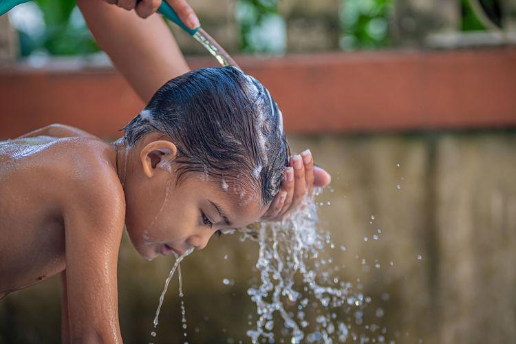 Full length of shirtless boy drinking water