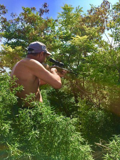 Full length of shirtless man holding tree