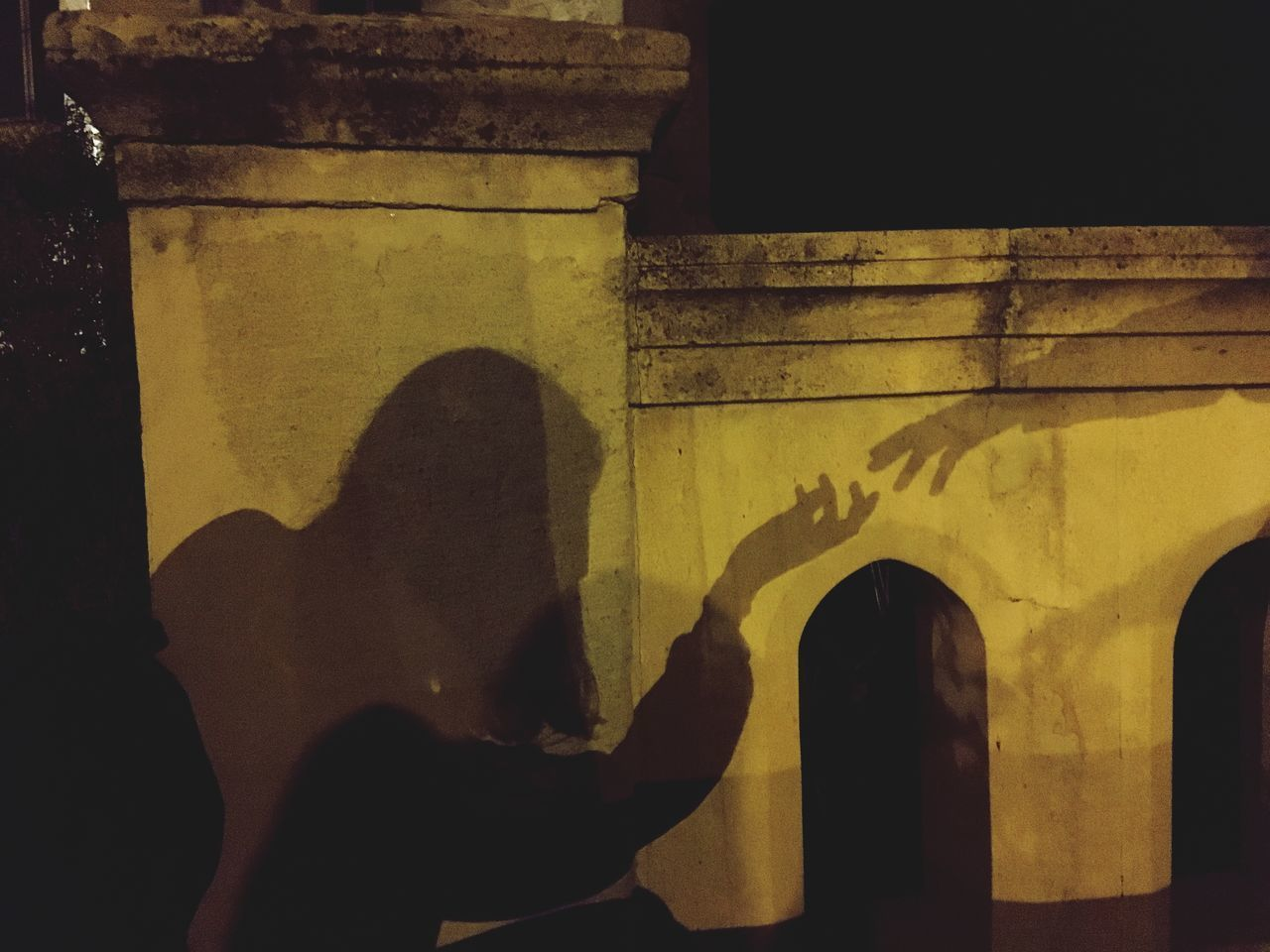 SHADOW OF PEOPLE STANDING ON WALL
