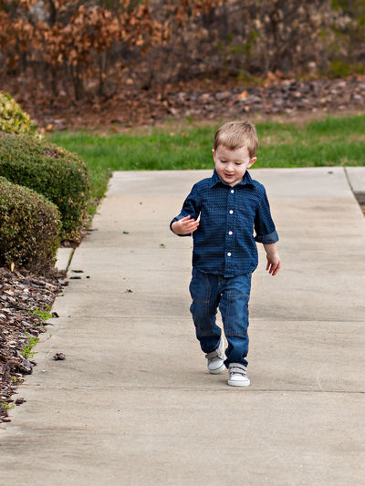 Front view of boy walking on garden path in park
