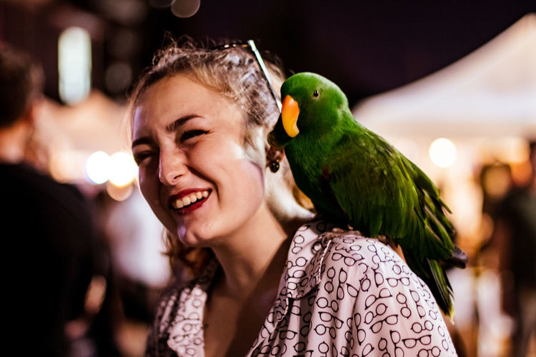 Close-up of happy woman with parrot on shoulder at night