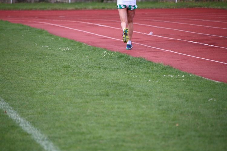 Low Section Of Man Running On Sports Track
