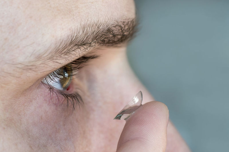 Cropped image of man putting contact lens