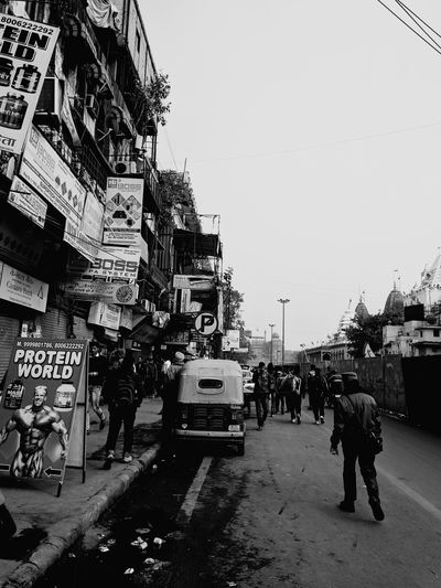 People on street in city against clear sky