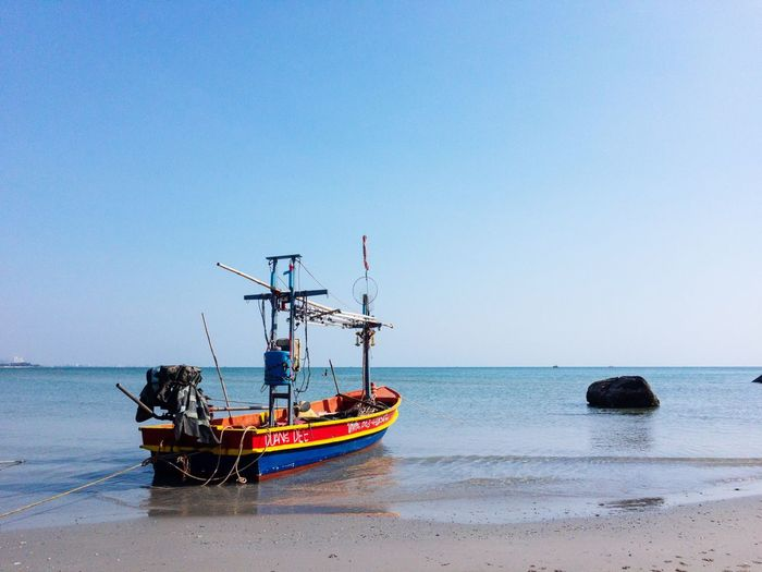 Fishing boat on sea against clear sky