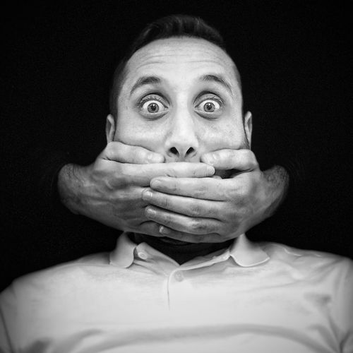 Cropped Hands Of Person Covering Mouth Of Man Against Black Background