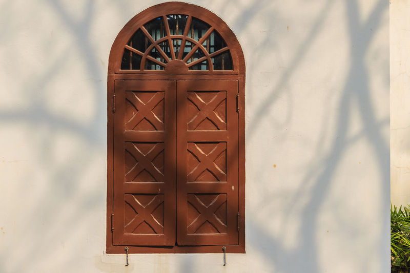 Old arched wooden window on white wall with shadows of tree branches. Shadow of a tree on the white wall with old arched window. White wall of the old building with arch window and shadows of trees. Arched Doorway Shadow And Light Shadow Of A Tree Arched Architecture Arched Entrance Arched Windows Architecture Brown Building Building Exterior Built Structure Close-up Day Design Floral Pattern Focus On Foreground Home Interior Metal Nature No People Pattern Shadow Shadow Of Tree Sunlight Wall - Building Feature White Wall White Wall With Shadows White Walled Buildings Window Wood - Material Wooden Window Wooden Window Box Wooden Window Frame Wooden Window Shutters Wooden Windows