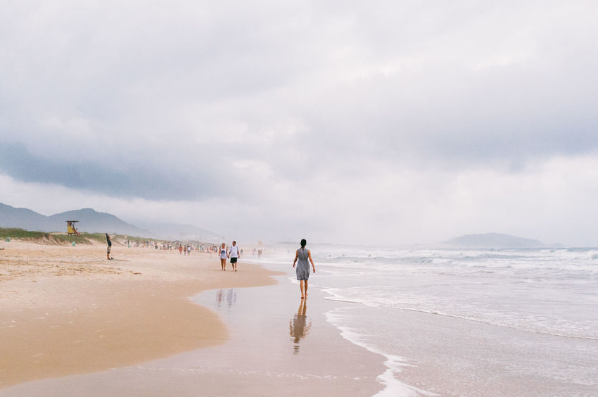 Adult Beach Beauty In Nature Brazil Cloud Cloud - Sky Day Florianópolis Full Length Leisure Activity Lifestyles Men Nature Outdoors Real People Sand Scenics Sea Sky Tranquility Vacations Walking Water Wave Young Woman