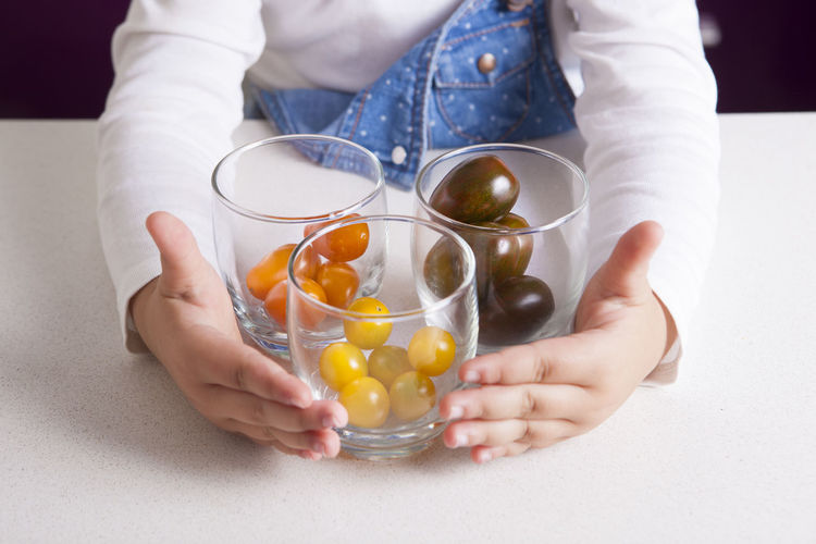 High angle view of girl sitting by glasses with cherry tomatoes on table