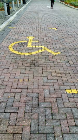 Text Communication Day Guidance Yellow High Angle View Outdoors Road No People Parking Lot Parking Sign Disabled Sign Wheelchair Sign