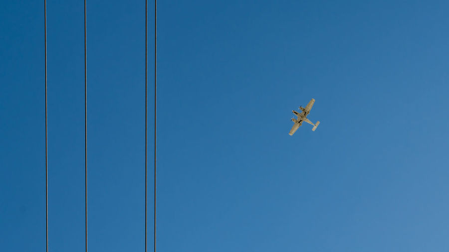 Low angle view of airplane flying in clear blue sky