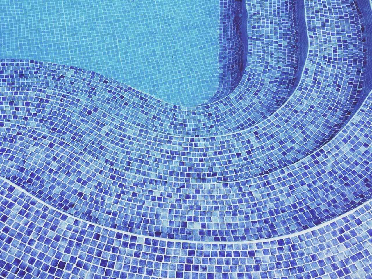 Close-up of cropped stairs in tiled swimming pool
