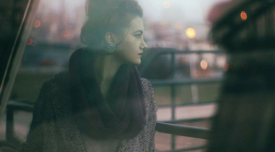 Young woman reflecting on glass window at dusk