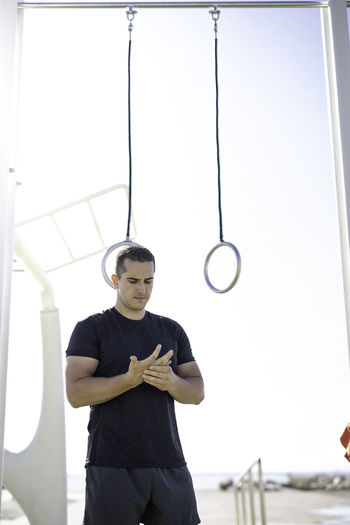 Man looking at aching hand while standing by gymnastic rings