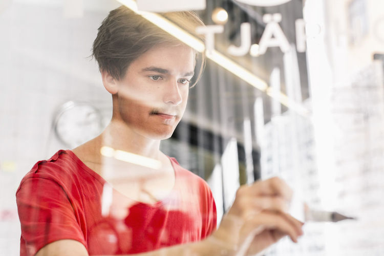 Portrait of young man working in glass