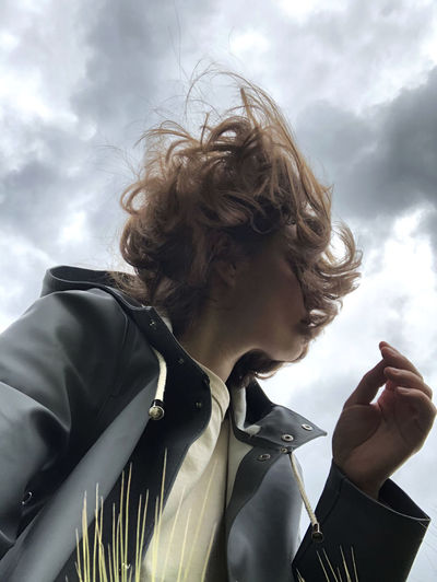 Low angle portrait of woman wearing hat against sky
