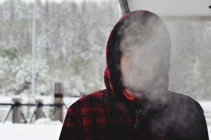 Man exhaling smoke during winter