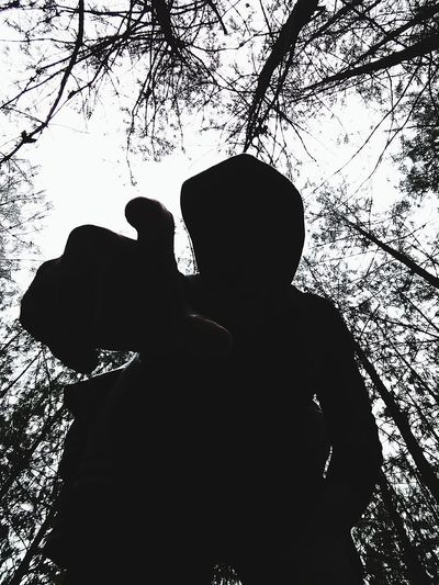 Rear view of silhouette man and woman standing by tree against sky