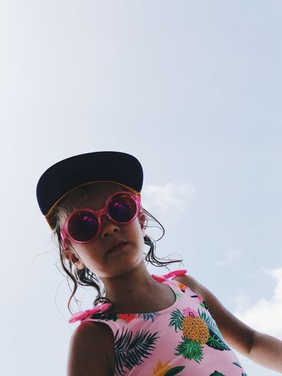 Low angle portrait of girl wearing sunglasses against sky