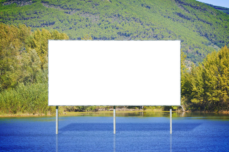 Blank advertising billboard against a calm lake Advertising Billboard Absence Advertisement Billboard Blank Business Finance And Industry Calm Lake Communication Copy Space Day Empty Frame Geometric Shape Land Marketing Message Nature No People Outdoors Placard Plant Sport Tree White Color