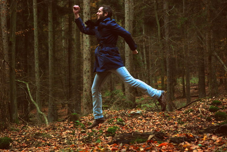 Full length of happy man in mid-air over fallen autumn leaves at forest