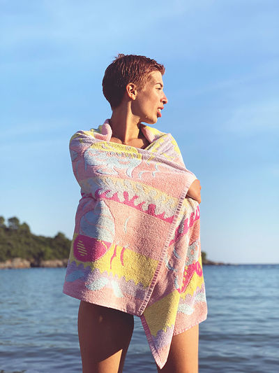 Woman wrapped in a towel while standing in sea against sky