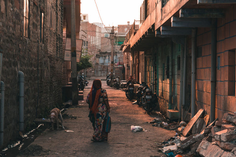 The blue city turning golden during the golden hour ... Travel Exploring Woman Real People Rear View Walking Jodhpur Bluecity Sunset Golden Hour Built Structure Streetphotography Streets Congestion Stray Rajasthan Walls Glowing City Architecture Built Structure Destruction Deserted Orange Color Sun Silhouette The Photojournalist - 2019 EyeEm Awards The Traveler - 2019 EyeEm Awards The Street Photographer - 2019 EyeEm Awards