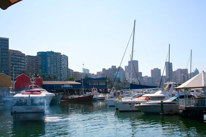 Architecture Boat Building Exterior Built Structure City Cityscape Clear Sky Day Durban Harbor Marine Mast Mode Of Transport Moored Nautical Vessel Outdoors River Sailboat Sky South Africa Transportation Water Waterfront