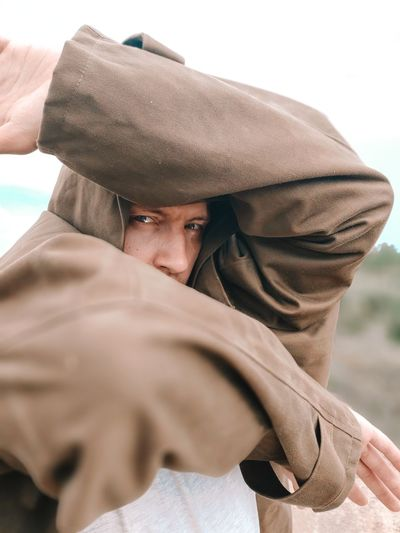 A man in a brown raincoat covers his face with his hands