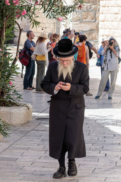 Jerusalem, Israel, July 14, 2017 : Religious Jew walks along the street and looks at his mobile phone in the old city of Jerusalem, Israel Adult City Day Holding Israel Jerusalem Jewish Lifestyles Looking Man Men Mobile Old Orthodox Outdoors People Person Phone Smart Smartphone Street Technology Traditional Urban Using