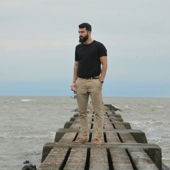Full length of young man looking at sea against sky
