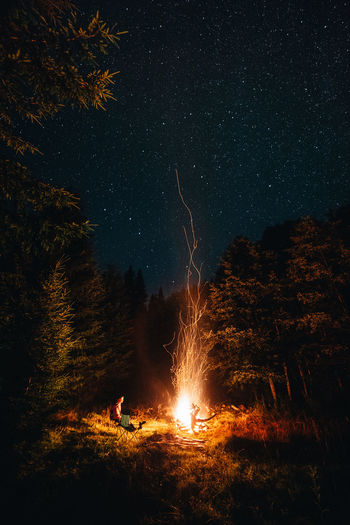 Woman sitting by fire on land against sky at night