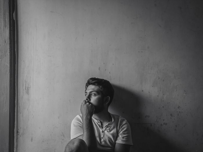Thoughtful young man looking away sitting against wall