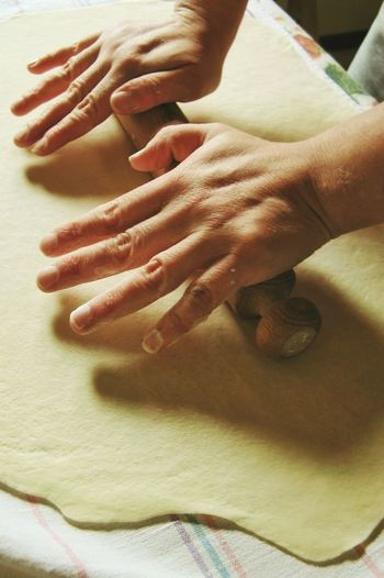 Cropped Image Of Hands Using Rolling Pin On Dough