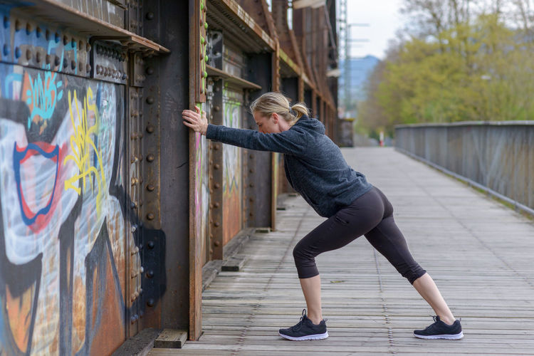 Side view of mature woman exercising on walkway